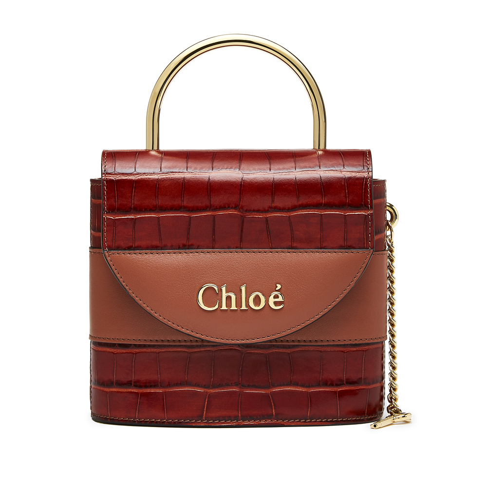 Chloé Chestnut Aby Lock Bag Chloé Chestnut Aby Lock Bag: This padlock-shaped silhouette borrows heavily from the Chloé archives—a modern riff on the maison's original Paddington bag. Structured to fit just the essentials, the croc-embossed chestnut leather looks luxe during the day and even better at night. There's no shortage of details to love here, from the tubular top handle to the delicate chain strap, to the gold key dangling off the side...100% calf leather Made in Italy.