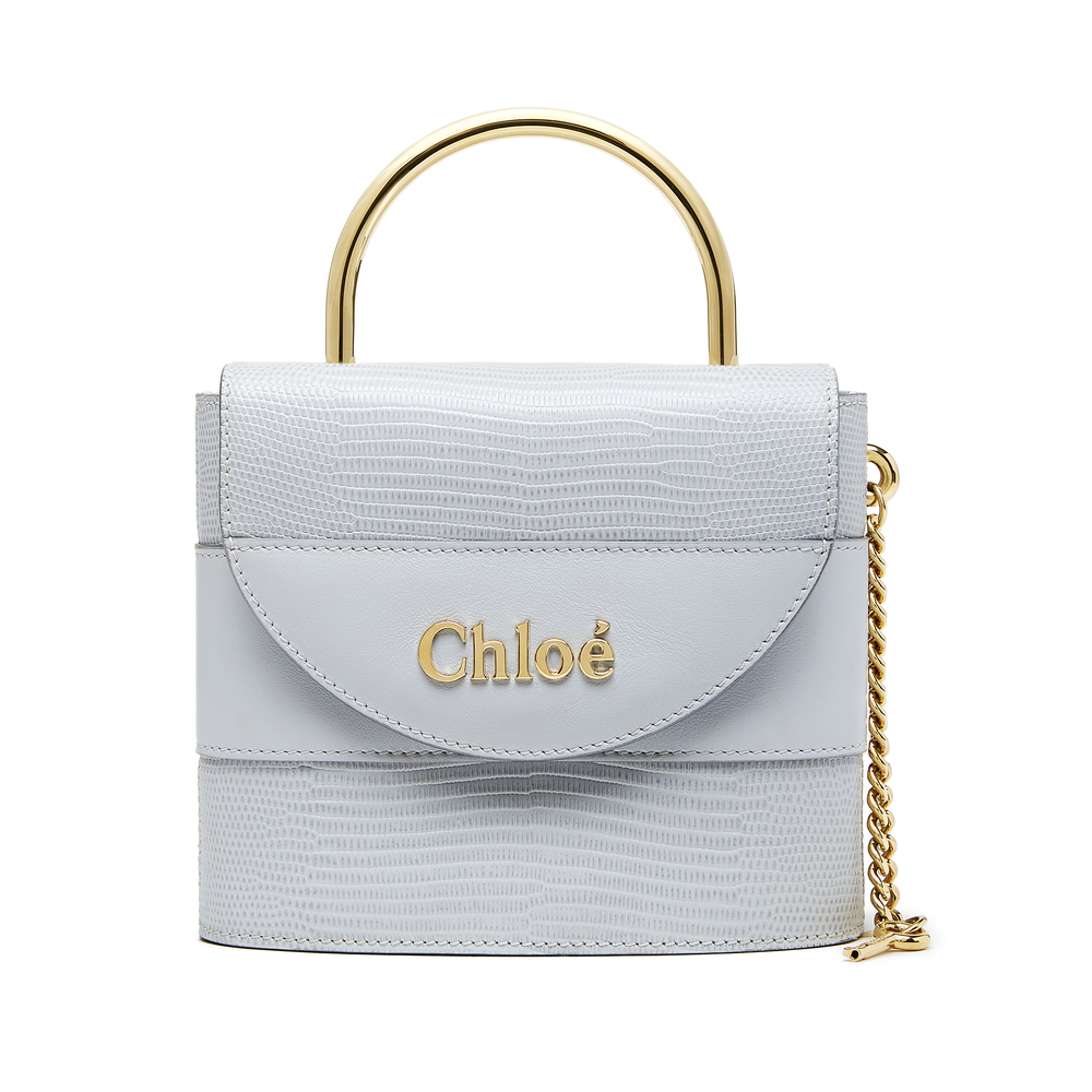 Chloé Aby Lock Bag in Light Cloud Chloé Aby Lock Bag in Light Cloud: This padlock-shaped silhouette comes from the Chloé archives—a modern riff on the maison's original Paddington bag. Rendered in the lightest-blue, lizard-embossed leather, it's sized just right for your everyday essentials (phone, keys, cardholder, lipstick) with no shortage of details to love, from the tubular top handle to the delicate chain strap, to the gold key dangling off the side...100% calf leather Made in Italy.